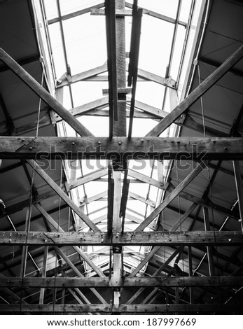 Monochrome old wooden factory roof framework structure with lit