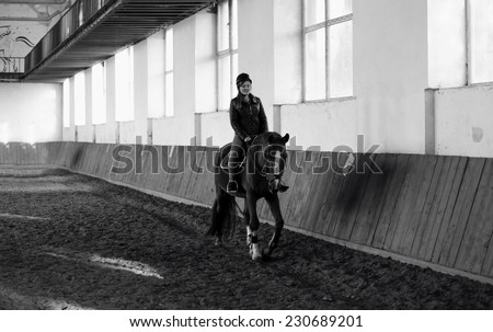Monochrome photo of woman riding horse at indoor manege - stock photo