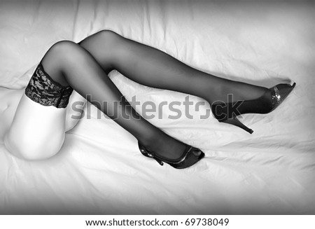 Monochrome photography of beautiful slim legs in black nylons. - stock photo
