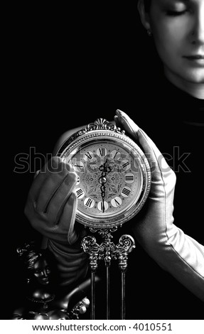 Monochrome picture of a beautiful girl with a clock (focus on clock) - stock photo