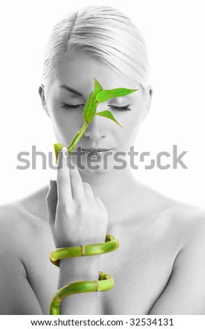 Monochrome picture of a beautiful woman with bamboo plant - stock photo