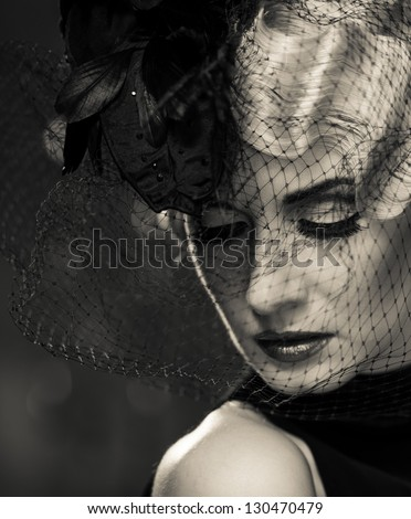 Monochrome picture of  elegant blond retro woman   wearing little hat with veil - stock photo