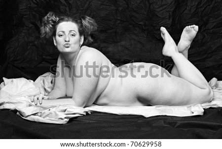 Monochrome picture of overweight woman on a  blanket. - stock photo