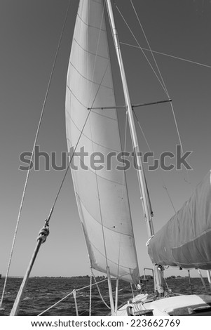 Monochrome picture of sailing yacht catches the wind. View on deck of sailing yacht. Picture from perspective of sitting on deck of yacht.
