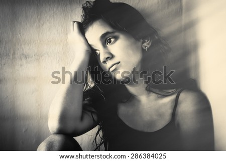 Monochrome portrait of a sad girl sitting in a corner with a dirty wall background - stock photo