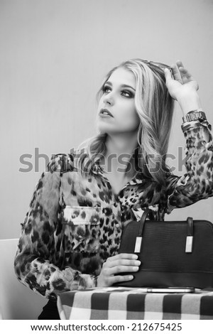 Monochrome portrait of beautiful blonde woman wearing animal print blouse and sunglasses seated at a restaurant table with a black handbag on it.