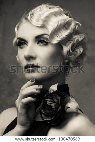 Monochrome portrait of elegant blond retro woman  in dress with beautiful rose flower - stock photo