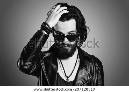 monochrome portrait of handsome man in leather jacket. Brutal bearded Sexy boy in sunglasses.rock and roll - stock photo