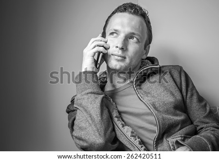 Monochrome portrait of sitting young adult Caucasian man talking on mobile phone - stock photo