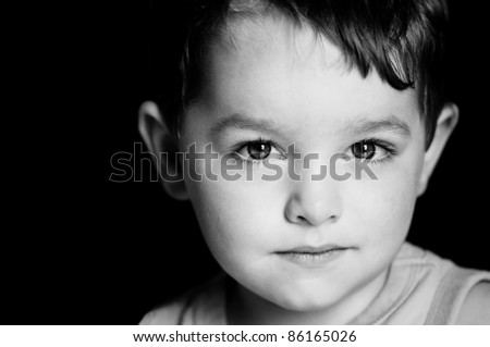 Monochrome portrait of young boy with serious expression - stock photo