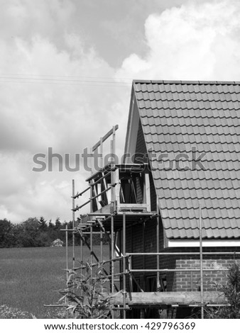 Monochrome scaffolding to the side of a new build residential house - stock photo