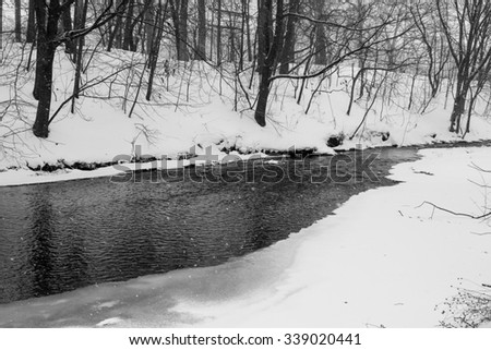 monochrome scene of a river during the winter season filled with snow