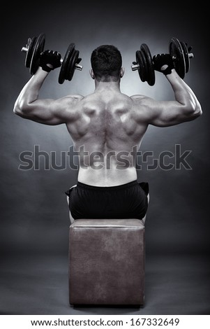 Monochrome shot of athletic young man working his deltoids with heavy dumbbells - stock photo