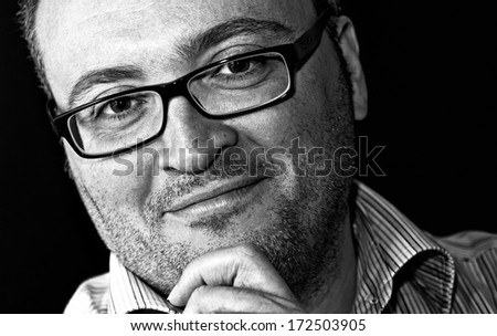 Monochrome shot smiling bespectacled bearded caucasian man against black background - stock photo