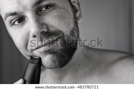 monochrome textured portrait bearded man shaving electric