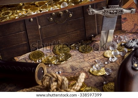 monocle, gold coins, diamonds, treasure chest, and a dagger on a treasure map - stock photo