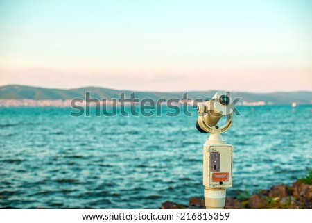 Monocular looking at the evening sea landscape - stock photo