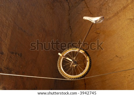 Monocycle in balance on metal rope.