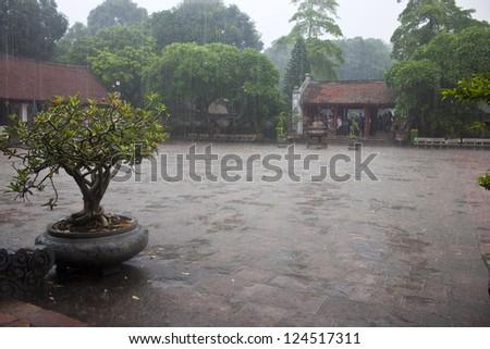 Monsoon rain at the temple of Literature in Hanoi, Vietnam. - stock photo