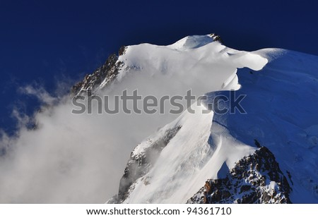 Mont Blanc du Tacul (4248 m) is a mountain in the Mont Blanc massif of the French Alps situated midway between the Aiguille du Midi and Mont Blanc - stock photo