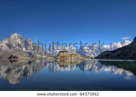 Mont Blanc Massif reflecting in Lake Blanc (Lac Blanc) above Chamonix, France. - stock photo