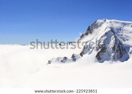 Mont Blanc mountain peak above low clouds - stock photo