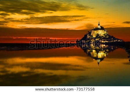 Mont Saint Michel abbey reflected in the bay at sunset, France - stock photo