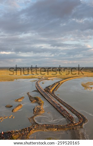 Mont Saint Michel, France - August 12: View of the road leading to Mont Saint Michel, France during a high tide at sunset on August 12, 2014.