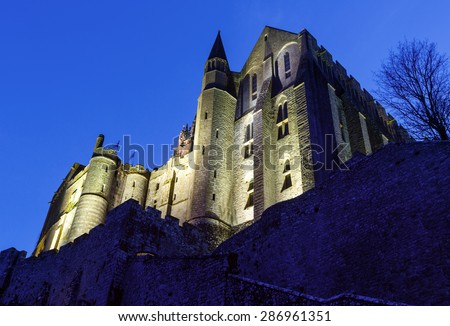Mont Saint-Michel night view.  Built in the XI-XVI centuries. The main facade of the church  built in the 12th century. Architect  William de Volpiano. - stock photo