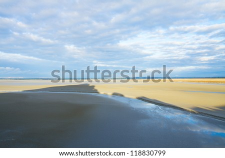 Mont Saint Michel shadow  over sand, France - stock photo