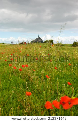Mont Saint Michel UNESCO heritage site. Poppy and daisy flowers field under cloudy sky. Tourists going towards Mont Saint Michel. Normandy, France. Selective focus in the central part of the field. - stock photo