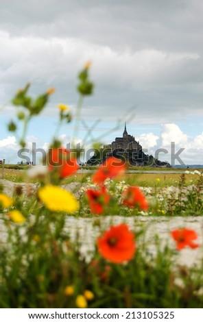 Mont Saint Michel UNESCO heritage site. Poppy flowers field under cloudy sky. Tourists going towards Mont Saint Michel. Normandy, France. Selective focus on the Mont Saint Michel. - stock photo