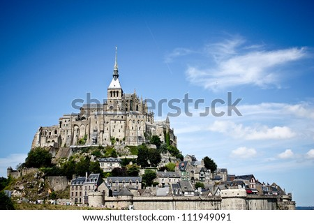 Mont St Michel world heritage in Normandy, France by the day - Famous historic place highest point in front of blue sky - stock photo
