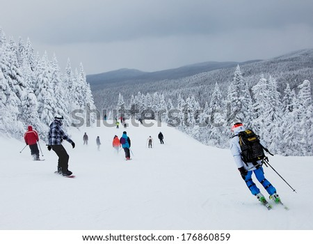 MONT-TREMBLANT, QUEBEC, CANADA -FEBRUARY 9: Skiers and snowboarders are sliding down an easy slope at Mont-Tremblant Ski Resort on February 9, 2014. It is the best ski resort in Eastern North America. - stock photo