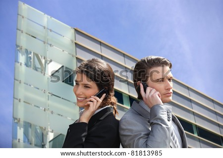 Montage of business couple in front of a modern building - stock photo