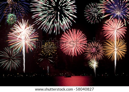 Montage of Independence Day fireworks with a boat in the foreground. - stock photo