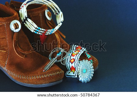 Montage of Native American Moccasins and handcrafted jewelry made from silver, turquoise,beads, antlers,horns, and coral. - stock photo