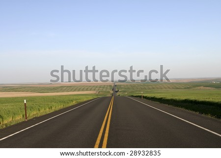 Montana highway with fields on both sides - stock photo