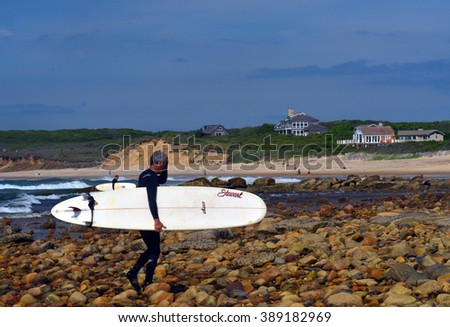 MONTAUK, NEW YORK-JUNE 13: Unidentified senior surfer with surfboard on Ditch Plains surfing beach, Altantic Ocean is seen on June 13, 2015. - stock photo