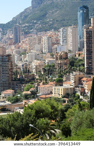 Monte Carlo, Monaco - September 20, 2015: aerial day view of city with high buildings and green trees on mountain slope beautiful weather on blue sky on cityscape background, vertical picture
