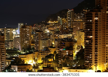Monte Carlo, Monaco - September 19, 2015: aerial night view of city with high buildings beautiful illumination street and area lighting palms on mountain slope on dark background, horizontal picture