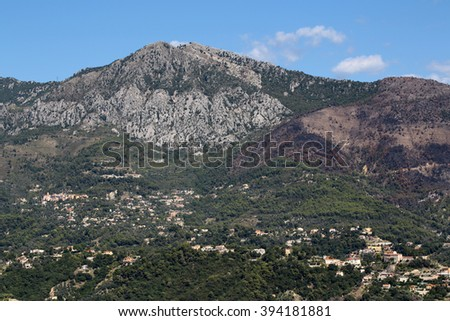 Monte Carlo, Monaco - September 20, 2015: view of mountain with densely populated city with residential buildings green trees on bright blue sky on landscape background, horizontal picture