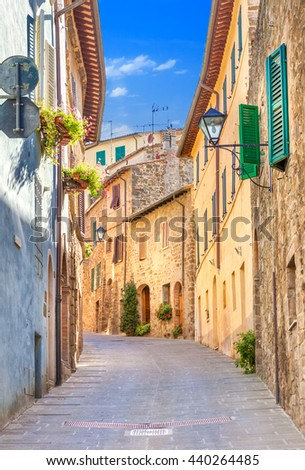 Montepulciano, Italy. Old narrow street lined with stone blocks in the center of town with colorful facades. Tourists walking along the street. - stock photo