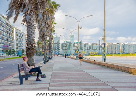 MONTEVIDEO, URUGUAY - MAY 04, 2016: people enjoying the afternoon on the board coast with the city as background.