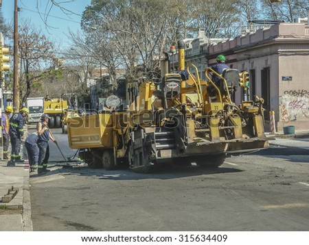MONTEVIDEO, URUGUAY, SEPTEMBER - 2015 - Workers and bulldozer working in a street in the city of Montevideo in Uruguay, South America.