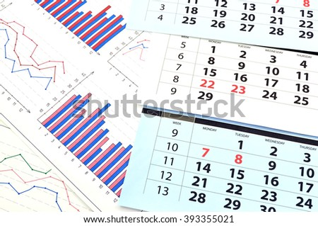 Monthly calendar and graphs on paper - stock photo