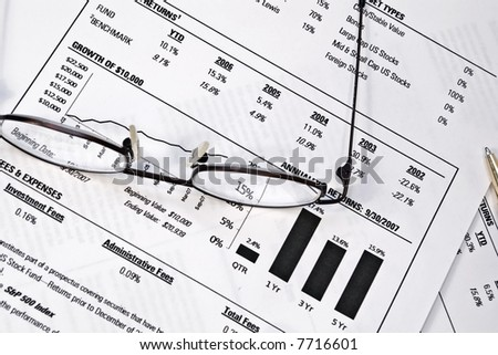 Monthly financial statement with pair of reading glasses - stock photo