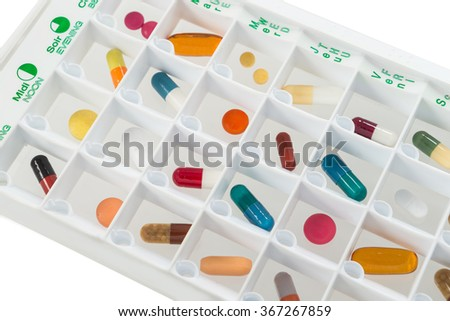 monthly pills planner with a daily dose of medications in each cell - stock photo