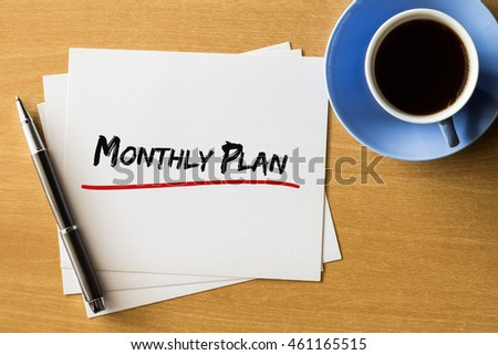 Monthly plan - handwriting on papers with cup of coffee and pen, business concept