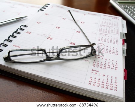 Monthly planner with reading glasses and pen on the table - stock photo